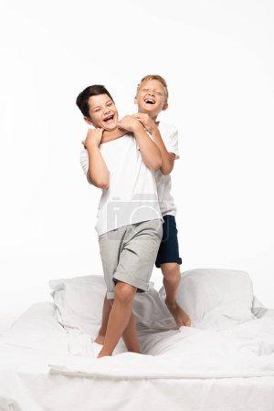 Photo pour Joyeux garçon blaguant étouffant frère souriant tout en se tenant debout sur le lit isolé sur blanc - image libre de droit