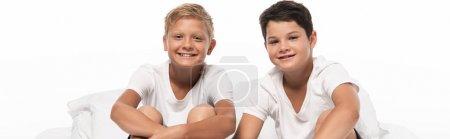 Foto de Foto panorámica de dos alegres hermanos sentados en la cama y mirando la cámara aislada sobre blanco. - Imagen libre de derechos