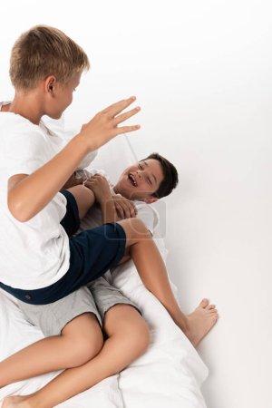 Photo pour Vue aérienne d'un garçon assis sur un frère qui rit tout en s'amusant au lit sur un fond blanc - image libre de droit