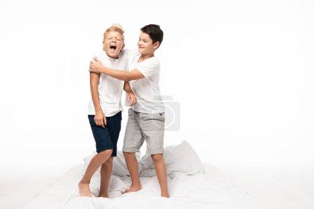 Photo pour Garçon joyeux blaguant tirant les cheveux de cris frère isolé sur blanc - image libre de droit
