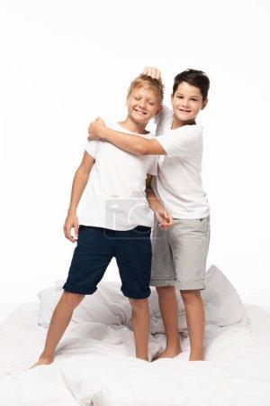 Photo pour Garçon gai serrant son frère dans ses bras et tirant ses cheveux à la blague alors qu'il est isolé sur le blanc - image libre de droit
