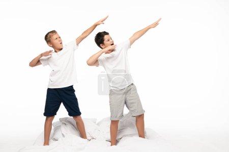 Photo pour Deux frères imitant le tir à l'arc debout sur le lit isolés sur le blanc - image libre de droit