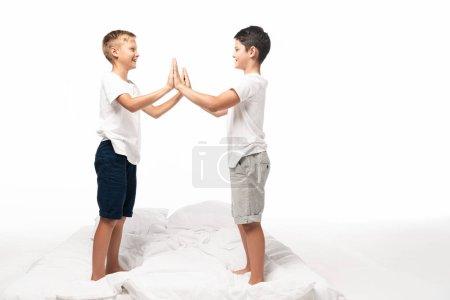 Photo pour Deux frères souriants serrant la main debout sur le lit isolés sur le blanc - image libre de droit