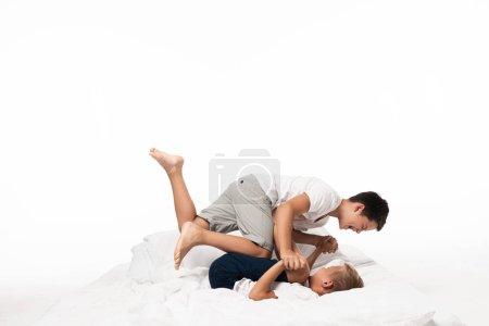 Photo pour Deux frères s'amusent en imitant se battre sur le lit isolé sur blanc - image libre de droit