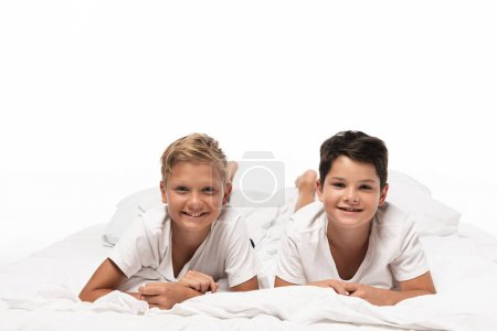 Photo for Two happy brothers lying on bed and smiling at camera isolated on white - Royalty Free Image