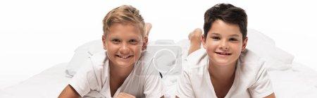 Foto de Foto panorámica de dos alegres hermanos acostados en la cama y sonrientes a cámara aislada sobre blanco. - Imagen libre de derechos