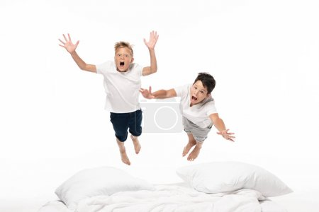 Photo for Two excited brothers levitating over bed and looking at camera isolated on white - Royalty Free Image