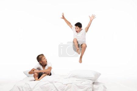 Photo pour Un garçon excité lévite un frère choqué assis sur sa literie isolé sur du blanc - image libre de droit
