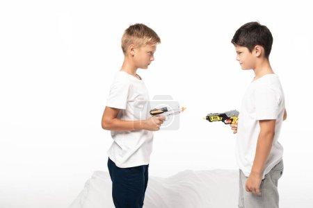Photo pour Deux frères se regardant l'un vers l'autre avec des pistolets jouets, debout sur le lit isolés sur blanc - image libre de droit