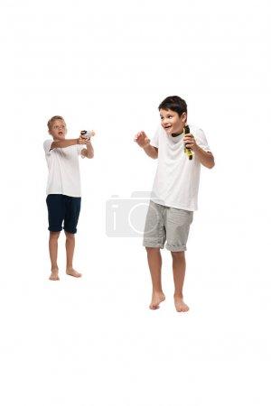Photo pour Garçon visant avec jouet pistolet à frère effrayé sur fond blanc - image libre de droit