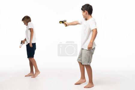 Photo pour Un garçon visant un frère effrayé sur fond blanc avec un fusil-jouet - image libre de droit