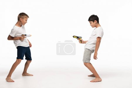 Photo for Two brothers aiming at each other with toy guns on white background - Royalty Free Image
