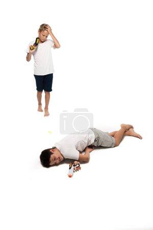 Foto de Muchacho que finge muerto cerca de un hermano disgustado sosteniendo armas de juguete sobre fondo blanco - Imagen libre de derechos