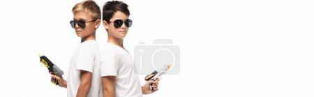 Photo pour Photo panoramique de frères portant des lunettes de soleil debout dos à dos, tenant des fusils-jouets tout en imitant des gangsters isolés sur du blanc - image libre de droit