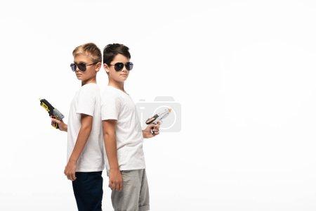 Photo pour Deux frères portant des lunettes de soleil debout, dos à dos, tenant des fusils jouets tout en jouant à des gangsters isolés sur - image libre de droit