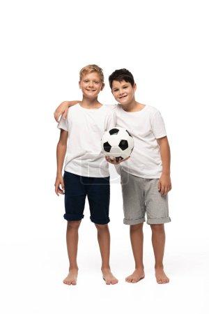 Foto de Chico alegre abrazando a hermano manteniendo el balón de fútbol en el fondo blanco. - Imagen libre de derechos