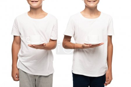 cropped view of two smiling brothers holding coffee cups isolated on white