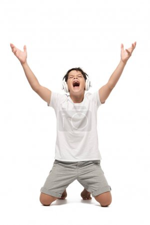 Photo for Excited boy standing on knees with raised hands while listening music in headphones and singing on white background - Royalty Free Image