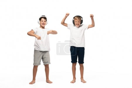 Photo pour Deux frères gentils qui écoutent de la musique dans des écouteurs et dansent sur fond blanc - image libre de droit