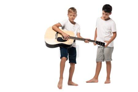 Foto de Niño de pie cerca de hermano tocando guitarra acústica sobre fondo blanco - Imagen libre de derechos