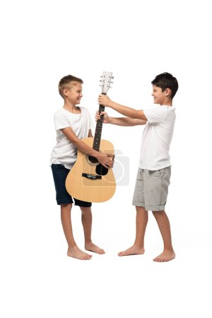 Photo pour Naughty boy taking guitar away from brother on white background - image libre de droit