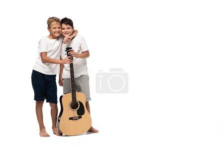 Photo pour Deux frères regardant la caméra et dansant tout en écoutant de la musique dans des écouteurs sur fond blanc - image libre de droit