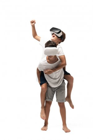 Photo for Cheerful boy piggybacking on brothers back and showing yes gesture while using vr headsets together on white background - Royalty Free Image