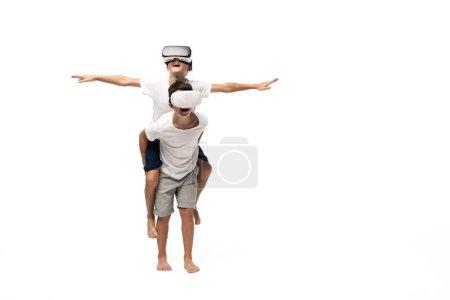 Foto de Chico sonriente usando auriculares vr mientras se masturba sobre los hermanos e imita volando sobre fondo blanco. - Imagen libre de derechos