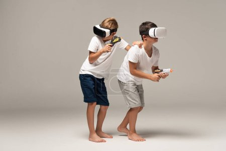 two barefoot brothers in pajamas holding toy guns while using vr headsets on grey background