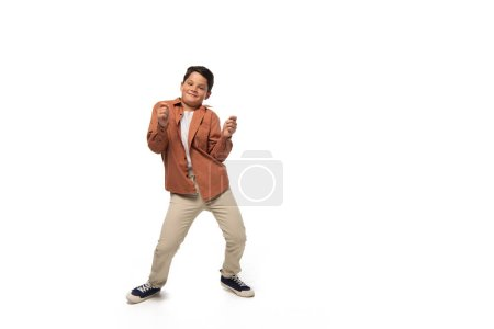 Photo for Cheerful boy dancing while looking at camera on white background - Royalty Free Image