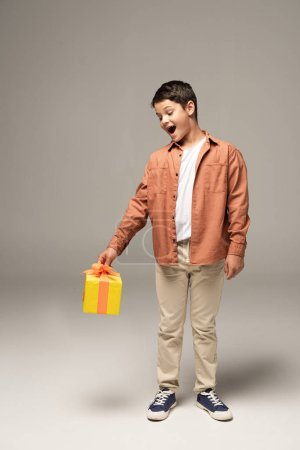 Photo for Excited boy holding yellow gift box while standing on grey background - Royalty Free Image