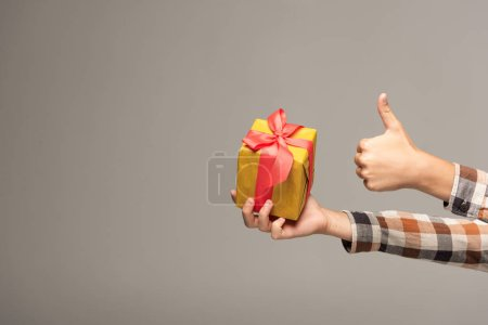Photo for Cropped view of boy holding yellow gift box and showing thumb up isolated on grey - Royalty Free Image