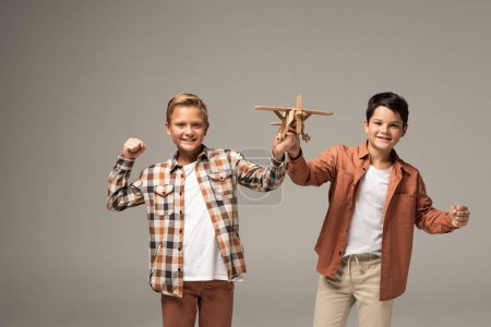 two cheerful brothers holding toy plane, showing yes gesture and looking at camera isolated on grey