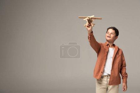Photo pour Garçon heureux tenant un avion-jouet en bois à main levée isolé sur gris - image libre de droit
