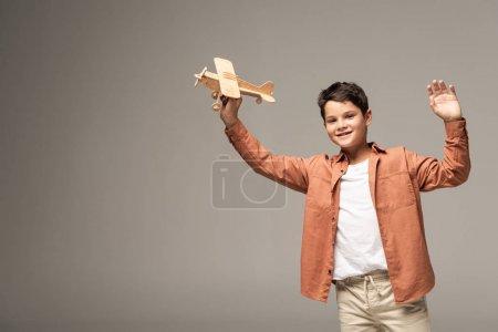 Photo pour Garçon souriant tenant avion jouet en bois et agitant la main à la caméra isolée sur gris - image libre de droit