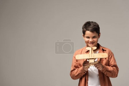 cheerful boy showing wooden toy plane and smiling at camera isolated on grey
