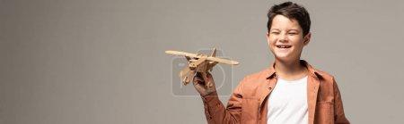 Foto de Foto panorámica del divertido niño que sostiene un avión de juguete de madera aislado en gris - Imagen libre de derechos