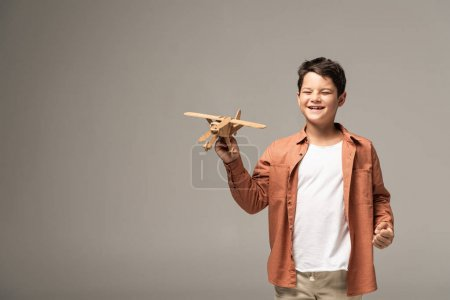 happy boy holding wooden toy plane and showing yes gesture isolated on grey