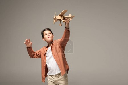 amused boy holding wooden toy plane in raised hand isolated on grey