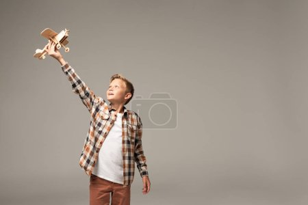 Photo for Happy boy holding wooden toy plane in raised hand isolated on grey - Royalty Free Image
