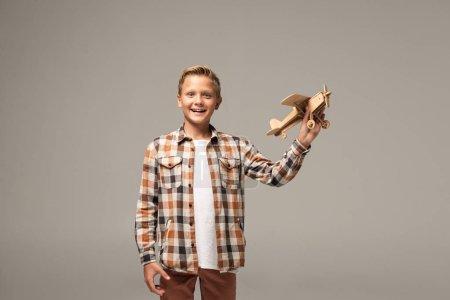 Photo pour Joyeux garçon tenant un avion-jouet en bois et souriant à une caméra isolé sur gris - image libre de droit