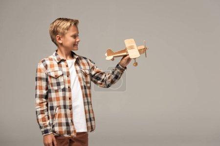 Photo pour Un garçon souriant tenant un avion-jouet en bois isolé sur gris - image libre de droit