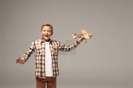 excited boy holding wooden toy plane and looking at camera isolated on grey