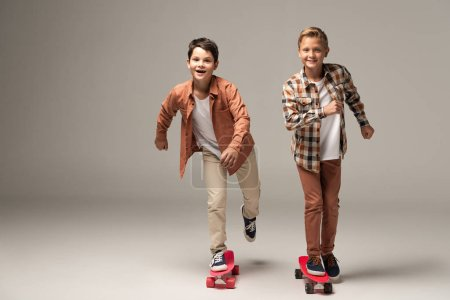 Photo for Two cheerful boys riding penny boards and smiling at camera on grey background - Royalty Free Image