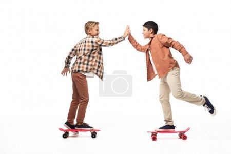 Photo pour Frères gais donnant haute cinq tout en chevauchant des planches de penny sur fond blanc - image libre de droit