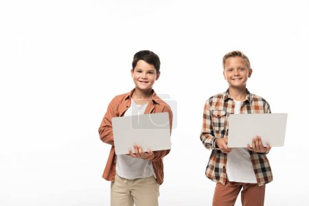 Photo for Two smiling brothers holding laptops and smiling at camera isolated on white - Royalty Free Image