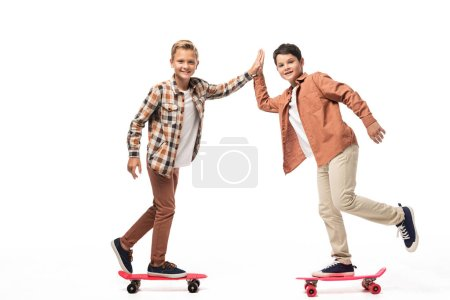 Photo for Cheerful brothers riding penny boards, giving high five and looking at camera on white background - Royalty Free Image