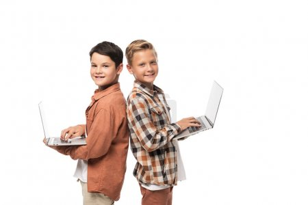 Photo for Two cheerful brothers holding laptops and looking at camera isolated on white - Royalty Free Image