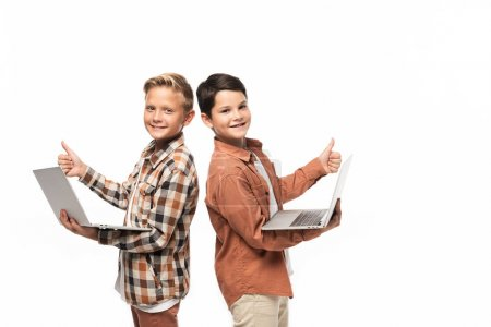 Photo for Two smiling brothers holding laptops, showing thumbs up and looking at camera isolated on white - Royalty Free Image