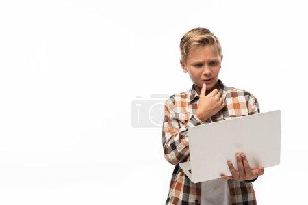 Photo pour Garçon réfléchi regardant ordinateur portable et tenant la main près du visage isolé sur blanc - image libre de droit